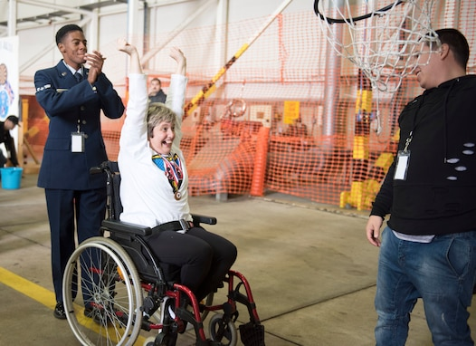 An athlete celebrates with her escort, Airman 1st Class Clarence Bennett, after scoring a basket at the 37th Joan Mann Special Sports Day at RAF Mildenhall, United Kingdom, Sept. 22, 2018.  Athletes from 28 local schools and organizations competed in 12 sporting events, including a basketball shot contest, wheel chair slalom, and a football toss competition. (U.S. Air Force photo by Senior Airman Lexie West)