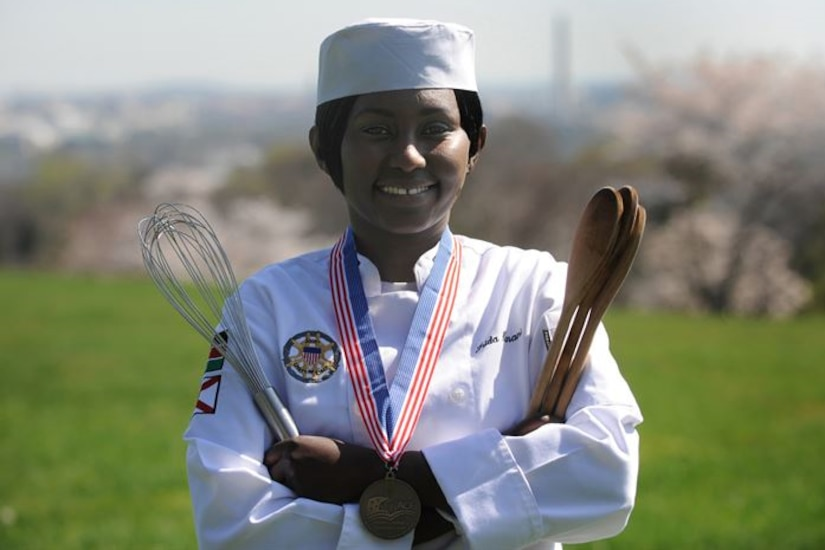 A Navy chef poses with a wisk and spoon.