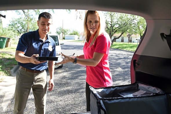 U.S. Air Force Col. Ricky Mills, 17th Training Wing commander, receives a meal from Meals for the Elderly Marketing and Event Director, Dannielle Dunagan, outside the house of a Meals for the Elderly recipient in San Angelo, Texas, Sept. 27, 2018. Mills delivered meals to 15 people, while assisting Dunagan with her route. (U.S. Air Force photo by Staff Sgt. Joshua Edwards/Released)