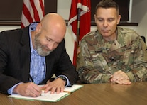 Tulsa District Commander, Col. Christopher A. Hussin watches as Tulsa County Levee Commissioner, Todd Kilpatrick signs the Feasibility Study Cost Sharing Agreement between the Tulsa District and the U.S. Army Corps of Engineers. The federal government has allocated $3 million to fund the total cost of the two year study, which will help the Corps of Engineers identify flood risk reduction solutions for the levee system.