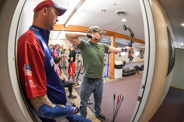Marine Lance Cpl. Ian Stairwalt from Wounded Warrior Battalion West at Camp Pendleton, Calif., aims his compound bow while Lance Thornton, a member of the U.S. Paralympic Archery Team, watches his technique Sept. 25, 2018, at Hill Air Force Base, Utah. Hill hosted the camp Sept. 24-28 through the Paralympic Military Program, which is run by the United States Olympic Committee in partnership with the U.S. Department of Defense and U.S. Department of Veterans Affairs. (U.S. Air Force photo by Cynthia Griggs)