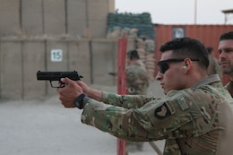 """German army Maj. Andreas Mehlhron, a field artillery officer, and officer in charge of the """"Schutzenschnur"""" event, coaches Spc. Anthony Addcock, a motor transportation specialist with the 101st Resolute Support Sustainment Brigade, while he fires the Koch P8 Pistol at Maholic Range on Bagram Airfield, Afghanistan, Sept. 14. (U.S. Army photo by: Spc. Alexes Anderson 101st Sustainment Brigade Public Affairs)"""