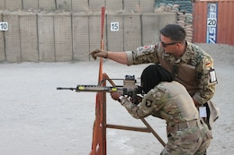 """German Sgt.1st Class Michael Michna, a combat medic and non-commissioned officer in charge of the """"Schutzenschnur"""" event coaches Pfc. Winshelle Pierre, an automated logistics specialist with the 101st Resolute Support Sustainment Brigade while she fires the HKG36 rifle at Maholic Range, on Bagram Airfield, Afghanistan, Sept. 14. (U.S. Army photo by: Spc. Alexes Anderson 101st Sustainment Brigade Public Affairs)"""