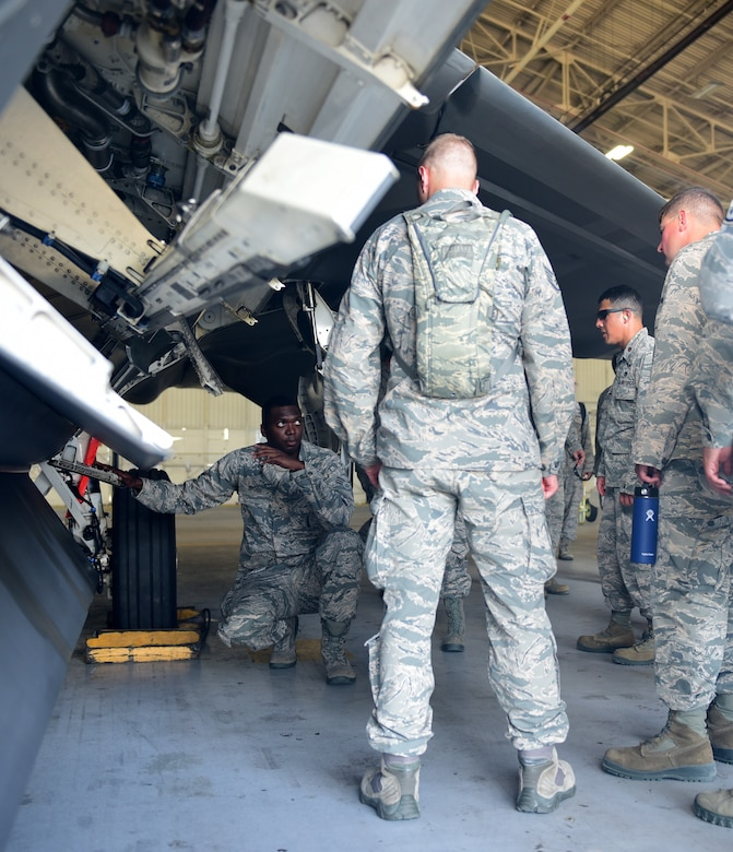 Airmen examine the operations of an F-22 Raptor munitons hull.