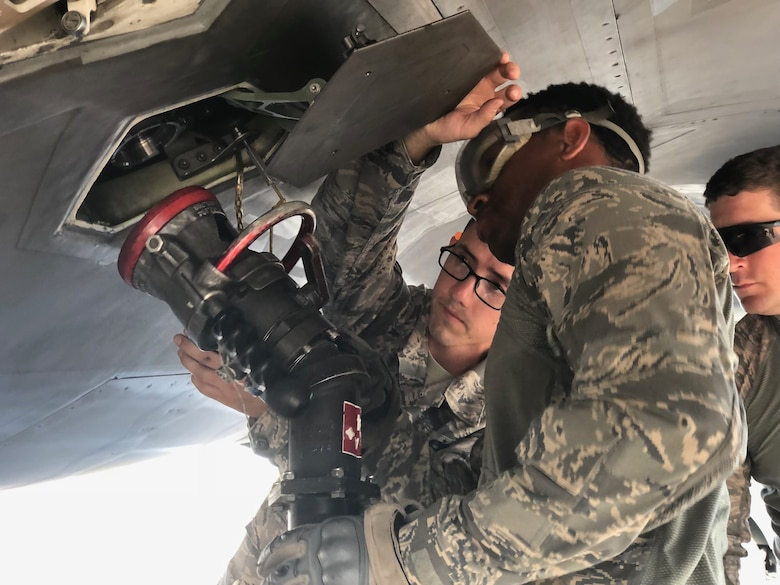 Staff Sgt. Cedric Koonce, assigned to the 78th Security Forces Squadron at Robins Air Force Base, Georgia, along with two other Airmen get the fuel hose lined up for refueling an F-22 Raptor during the Combat Support Wing Exercise 18 September at Moody Air Force Base, Georgia.