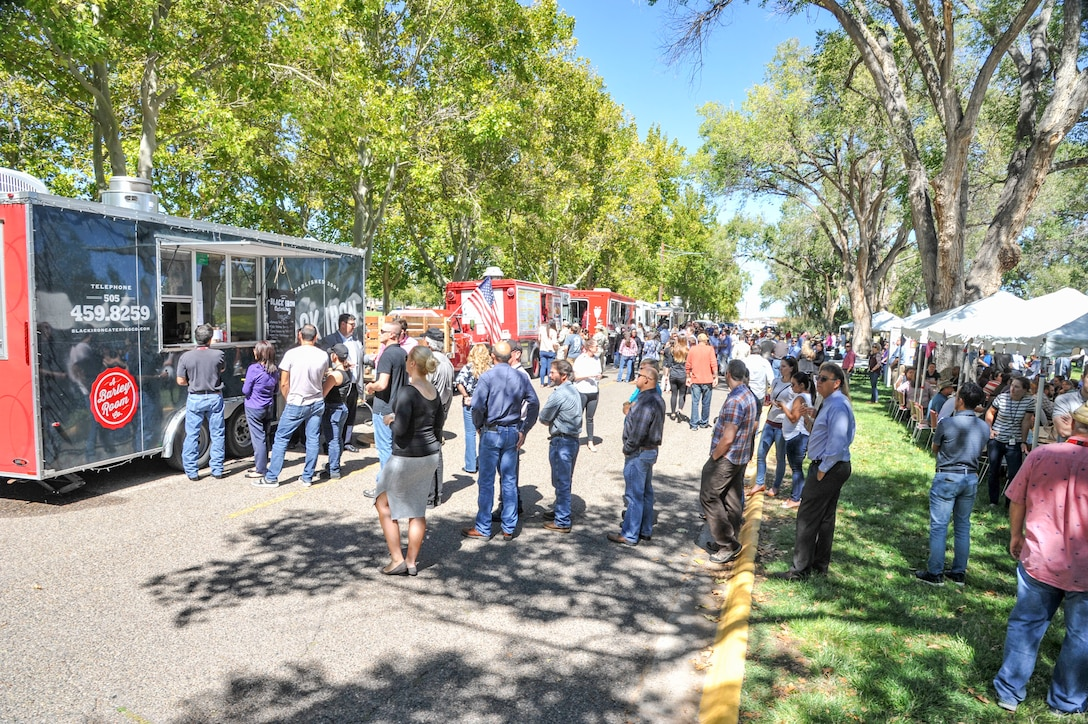 People queue for food trucks at the 2018 Hispanic Heritage Diversity Day event at Hardin Field here Sept. 27. This year's event featured keynote speaker Albuquerque DA Raul Torrez, the Al Hurricane Jr. Band. There was also a car show, an art show, and a samba sizzle Latin dance workout. (U.S. Air Force photo by Jim Fisher)