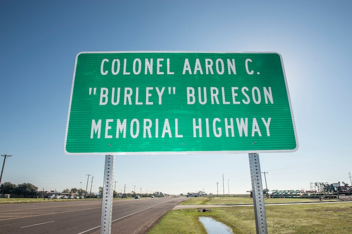 """A sign is dedicated to the late U.S. Air Force Col. (Ret.) Aaron C. """"Burley"""" Burleson, former commander of the 97th Air Mobility Wing, Sep. 28, 2018, at Altus, Okla. To honor his achievements to the Altus community and 97th AMW, the portion of State Highway 62 beginning at County Road 206 and extending east to County Road 210 in Jackson County was named after him. (U.S. Air Force photo by Senior Airman Cody Dowell)"""