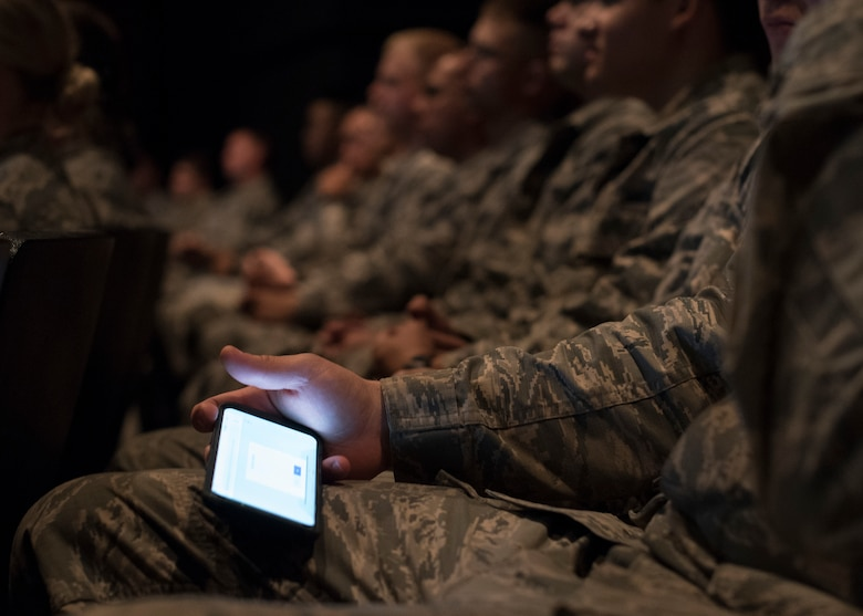 Airmen attending a base all-call use their smart phones to follow along and interact during the presentation at Fairchild Air Force Base, Washington, Sept. 26, 2018. Fairchild leadership supporting Airmen is a high priority, and were testing out the interactive format as a means to better connect with Airmen. (U.S. Air Force photo/Senior Airman Ryan Lackey)