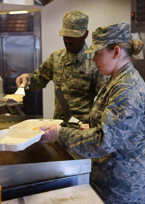 Airman Hana Parker (right), 9th Force Support Squadron food service specialist, helps her coworkers during the lunch shift at Beale Air Force Base, California, Sept. 27, 2018. Airmen from 9th FSS continue to work efficiently since moving from the Contrail Dining Facility to the Ramoneda Grill during the renovation. (U.S. Air Force photo by Senior Airman Morgan Brown)