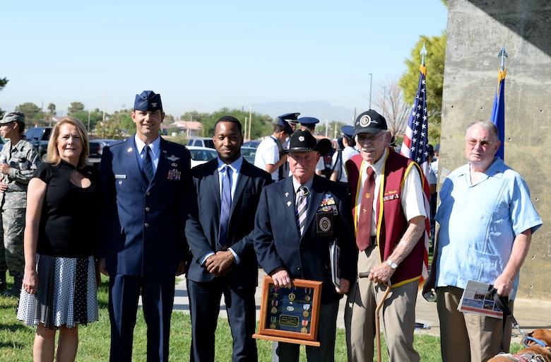 Attendees of the Prisoner of War/Missing in Action ceremony stand for a picture at Freedom Park on Nellis Air Force Base, Nev., Sept. 21, 2018. Newt Hiesley used his son, who was medically discharged from the military, as the man on the flag. (U.S. Air Force photo by Airman 1st Class Bryan T. Guthrie)