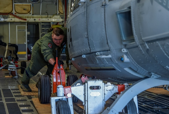 U.S. Air Force Staff Sgt. Cameron Morris, 4th Airlift Squadron loadmaster, helps push a U.S. Marine Corps UH-1Y Venom off a C-17 Globemaster III at Václav Havel Airport Prague, Czech Republic, Sept. 10, 2018. Morris, other 4th AS Airmen and ten marines worked together to load and offload the helicopter at various destinations. (U.S. Air Force photo by Senior Airman Tryphena Mayhugh)