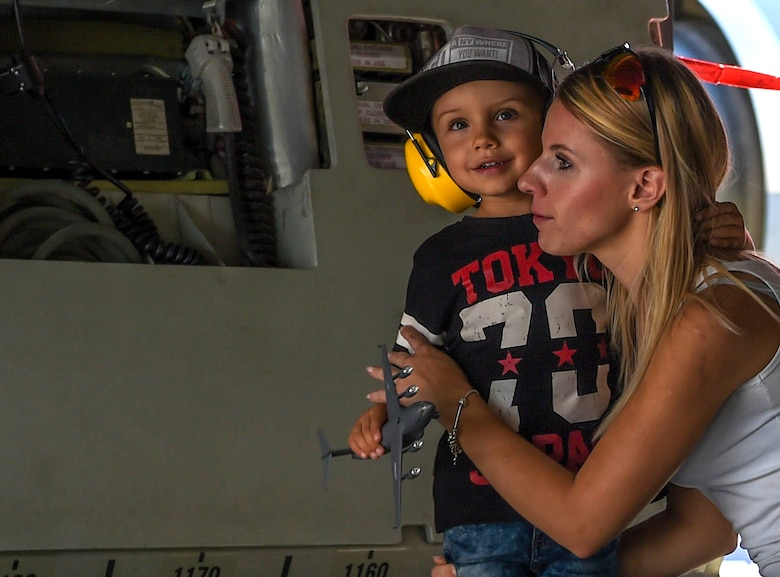 A child holds a model of a C-17 Globemaster III while touring inside a McChord Field, Wash., C-17 during the NATO Days Air Show in Ostrava, Czech Republic, Sept. 16, 2018. Patrons of the air show were able to walk inside the aircraft and ask 4th Airlift Squadron Airmen questions about the plane. (U.S. Air Force photo by Senior Airman Tryphena Mayhugh)