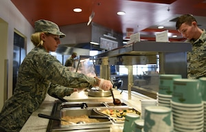 Airman 1st Class Chelsea Tansley, 9th Force Support Squadron food service specialist, services food to a customer for lunch at Beale Air Force Base, California, Sept. 27, 2018. The Contrails Dining Facility is expected to be completed March, 2019. (U.S. Air Force photo by Senior Airman Morgan Brown)
