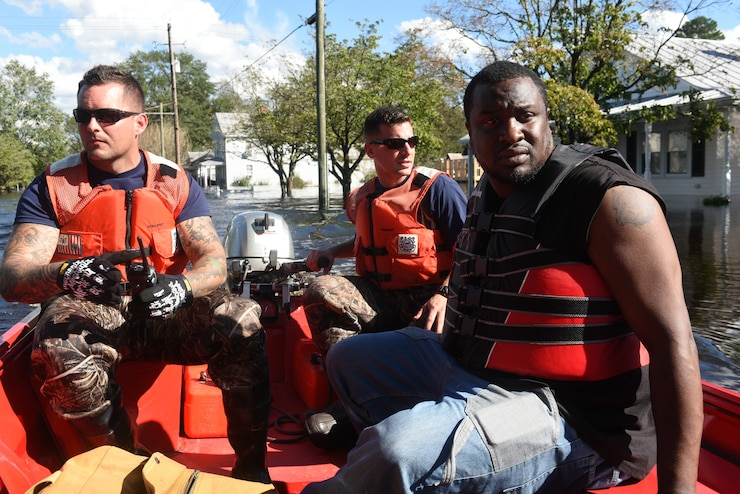 A Coast Guard boat crew assists Bernard Jones (right) in safely getting to his house Tuesday, September 18, in Pollocksville, North Carolina. Jones and his family left their home before Hurricane Florence flooded the town, leaving many buildings completely submerged.
