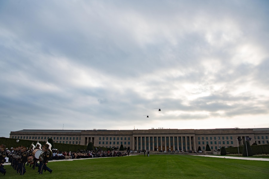 Two helicopters fly over the Pentagon as military musicians march on the parade field.