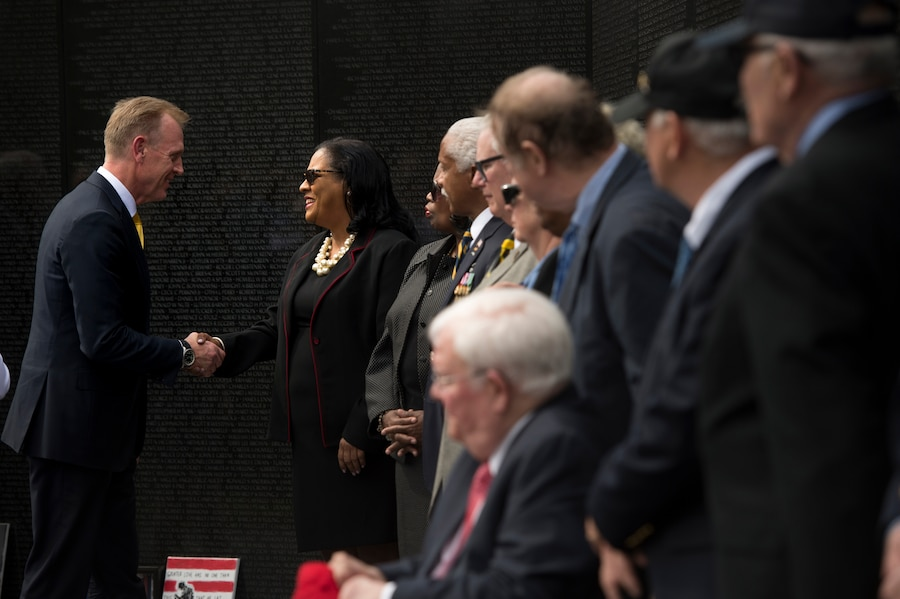 Deputy Defense Secretary Patrick M. Shanahan shakes hands with a woman as other civilians watch.