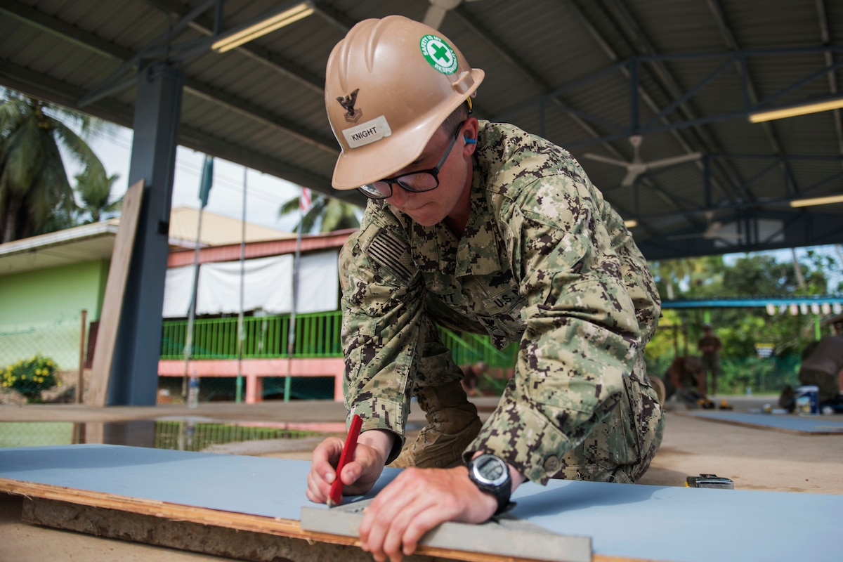 A sailor measures building materials.