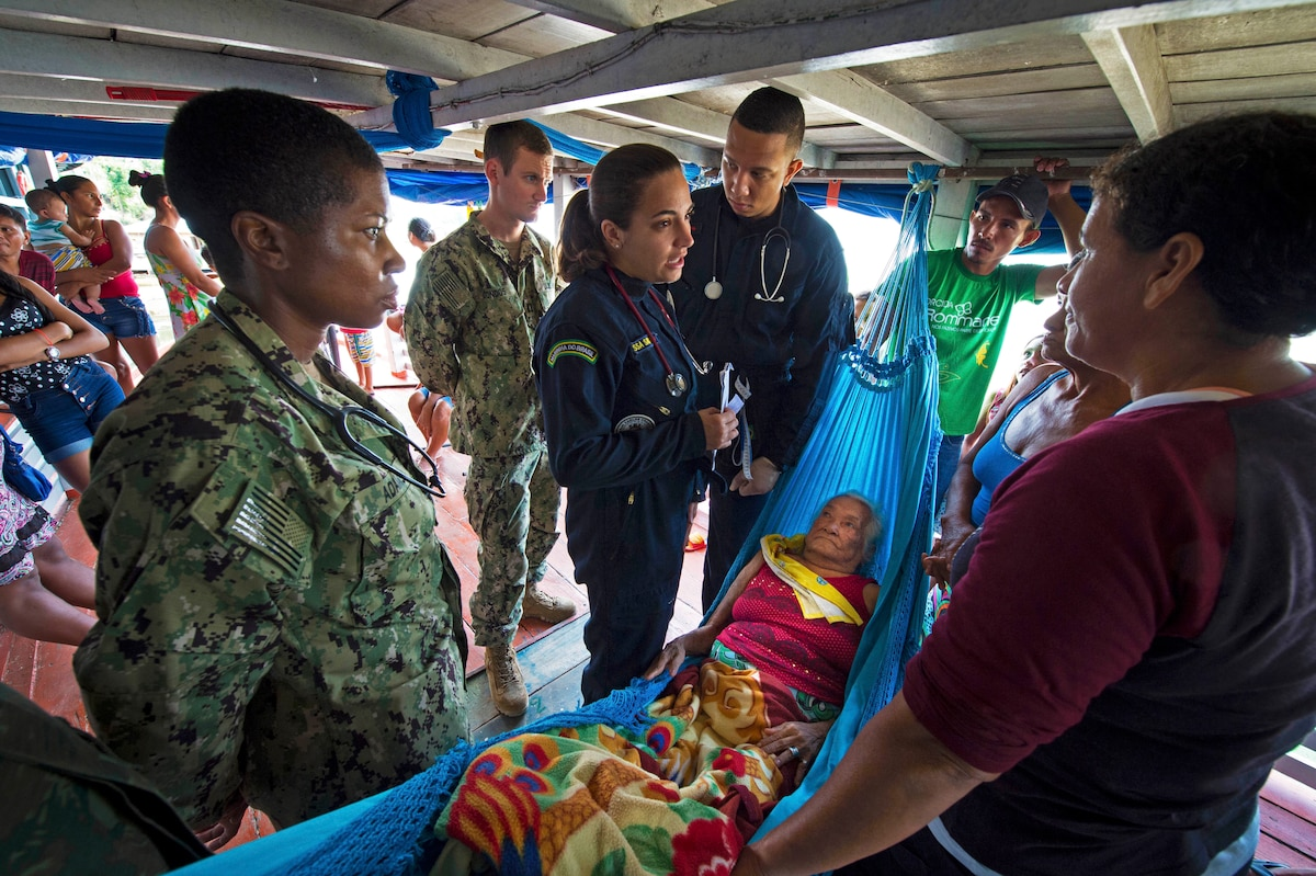 Several service members stand around a patient in a hammock.