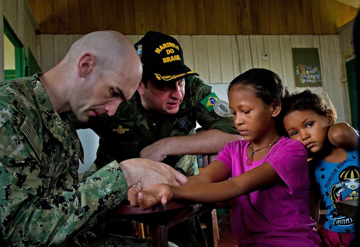 Navy Lt. Cmdr. Thomas Barlow examines a child's hand.