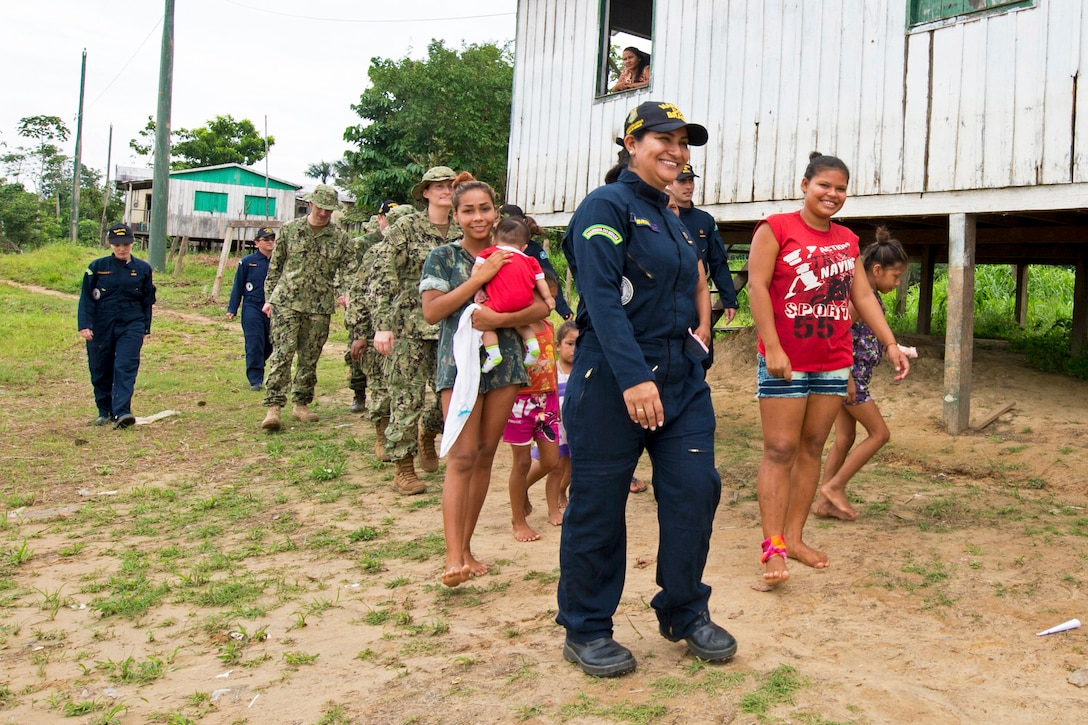 A team of U.S. and Brazilian navy doctors walk with residents in a Brazilian village.