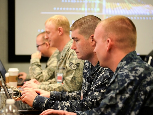 Candid photograph of four CDX military participants concentrating at computers