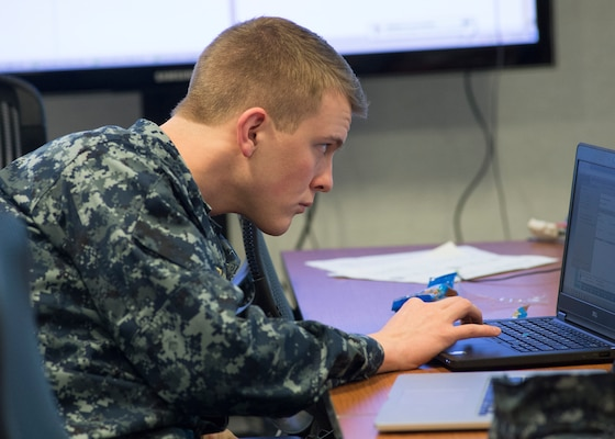 A member of the Red Cell studies his computer screen intently as he challenges participants' cyber defense  skills.
