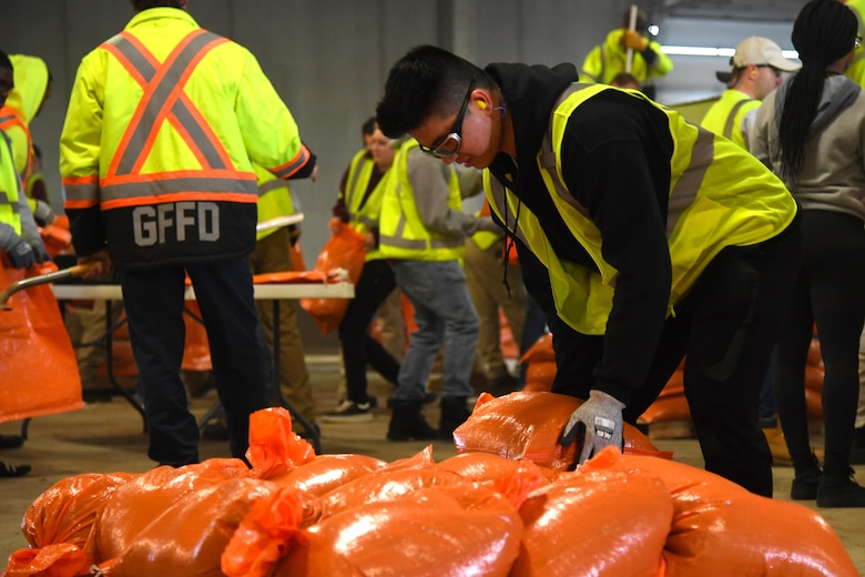Airman 1st Class Ninghui Fang, 319th Force Support Squadron food services apprentice, stacks a completed sandbag onto a pallet during a sandbag stockpile volunteer event March 28, 2019, in Grand Forks, North Dakota. Nearly 60 Grand Forks Air Force Base members worked together to fill several thousand sandbags in preparation of expected flooding. (U.S. Air Force photo by Senior Airman Elora J. Martinez)