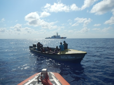 Coast Guard Cutter Hamilton small boat crew boards a suspected smuggling vessel while the Hamilton maintains security in the background March 22, 2019, in the Caribbean Sea.