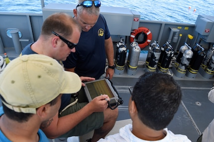 Force Master Diver Scott Brodeur, Naval Expeditionary Combat Command, watches as Chief Navy Diver Marshall Goble tries out the Office of Naval Research TechSolutions-sponsored Scuba Binary Dive Application during a demonstration and evaluation off the coast of Panama City, Fla.