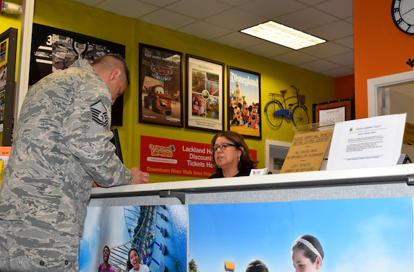 Diana Gonzalez, a sales associate at Joint Base San Antonio-Lackland's Information, Tickets and Travel office helps Master Sgt. Juan Rodriguez select seats for a sporting event. (U.S. Air Force photo by Debbie Aragon)