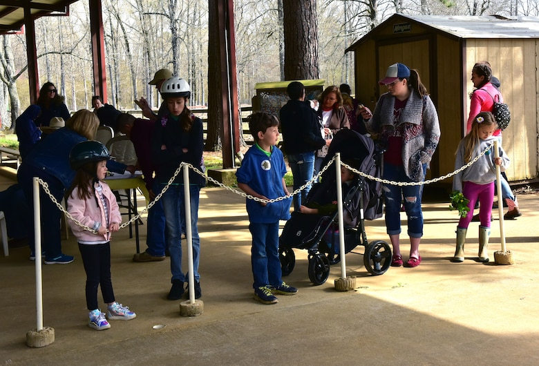 Children and adults line up behind a white chain to ride horses.