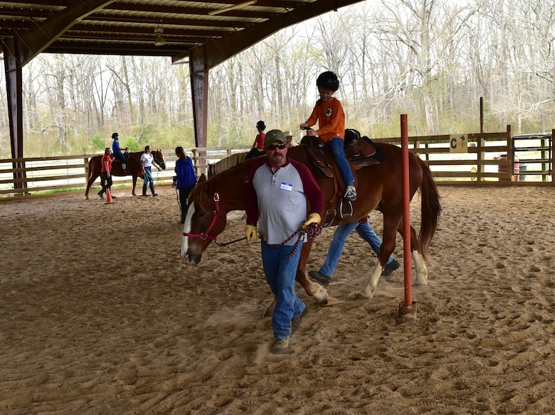 Male and female adults lead children on horseback around a dirt riding ring enclosed with a wooden fence.
