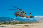 A Black Hawk helicopter, equipped with an aerial water bucket, from the Chief Warrant Officer 5 David R. Carter Army Aviation Support Facility at Buckley Air Force Base, Aurora, Colorado, departs the Spring Fire helibase, in Fort Garland, Colorado, to support fire suppression efforts July 3, 2018.  On order of the Governor, the standing Joint Task Force - Centennial commands and integrates CONG forces to support civil authorities in assisting Colorado, or supported states, during times of crisis and disaster, to save lives, prevent suffering, and mitigate great property damage. (U.S. Air National Guard photo by Tech. Sgt. Nicole Manzanares)