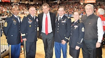 CSM Torenzo Davis, MG Troy Kok, Mr. Mike Bohn, MAJ Ryan Blake, SGM Kimberly Hart, Mr. Stephen Lee- photo taken end court during pregame for the University of Cincinnati basketball game. 6 people gather for a group photo on the bearcats basketball floor. Three men are in uniform, one female in dress blue army uniform. The man in the middle is wearing a black suit and red tie.