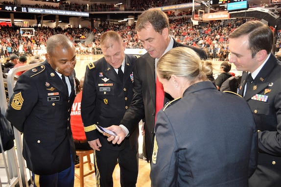 Left to right; CSM Torenzo Davis, MG Troy Kok, Mr. Mike Bohn, SGM Kimberly Hart, MAJ Ryan Blake- Mr. Mike Bohn sharing photos from his cellular phone from his recent visit to the Pentagon during the pregame of the University of Cincinnati basketball game. Men and woman in Army dress blue uniform staring at a cell phone during a college basketball game on the courtside.