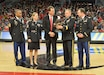 CSM Torenzo Davis, SGM Kimberly Hart, Mr. Mike Bohn, MG Troy Kok, MAJ Ryan Blake- Standing center court for eagle presentation during half time of the University of Cincinnati basketball game. They're standing on the center court giant black C for Cincinnati presenting the man in the middle with an award that a big bald eagle.