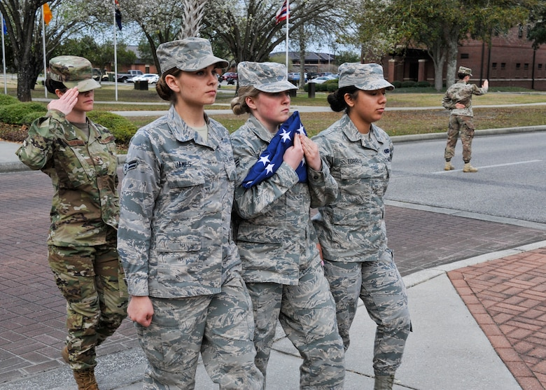 Airmen carry the U.S. flag during an all-female flight retreat ceremony March 8, 2019, at Joint Base Charleston, S.C.
