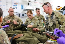 Spc. Alyson Rausch, 452d Combat Support Hospital, inspects mock casualty's injuries during the Golden Trident mass casualty training exercise at Camp Arifjan, Kuwait, March 21, 2019.