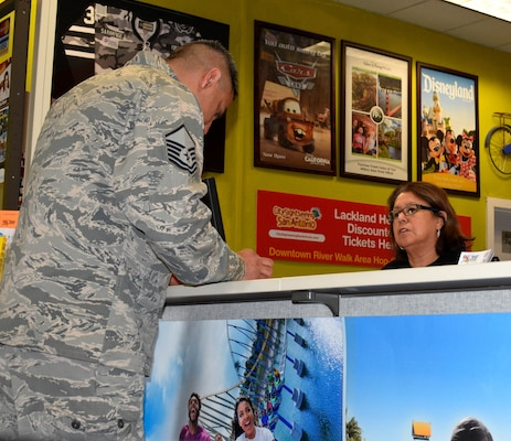 Diana Gonzalez, Joint Base San Antonio-Lackland's Information, Tickets and Travel Office sales associate, helps Master Sgt. Juan Rodriguez, a 26th Aerial Port Squadron member, select seats for a sporting event.