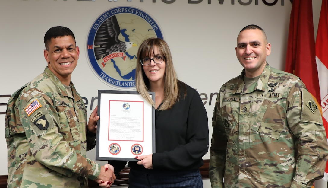 """Transatlantic Division Commander Col. Mark C. Quander (left) and Command Sergeant Major Randolph Delapena (right) present the TAD """"Employee of the Year"""" Award for 2018 to Rachael Raposa, TAD's Regional Contracting Chief, during a ceremony held in Winchester, Va., on March 28, 2019. Quander praised Raposa for her contracting expertise, world-class contracting support, and volunteer spirit."""