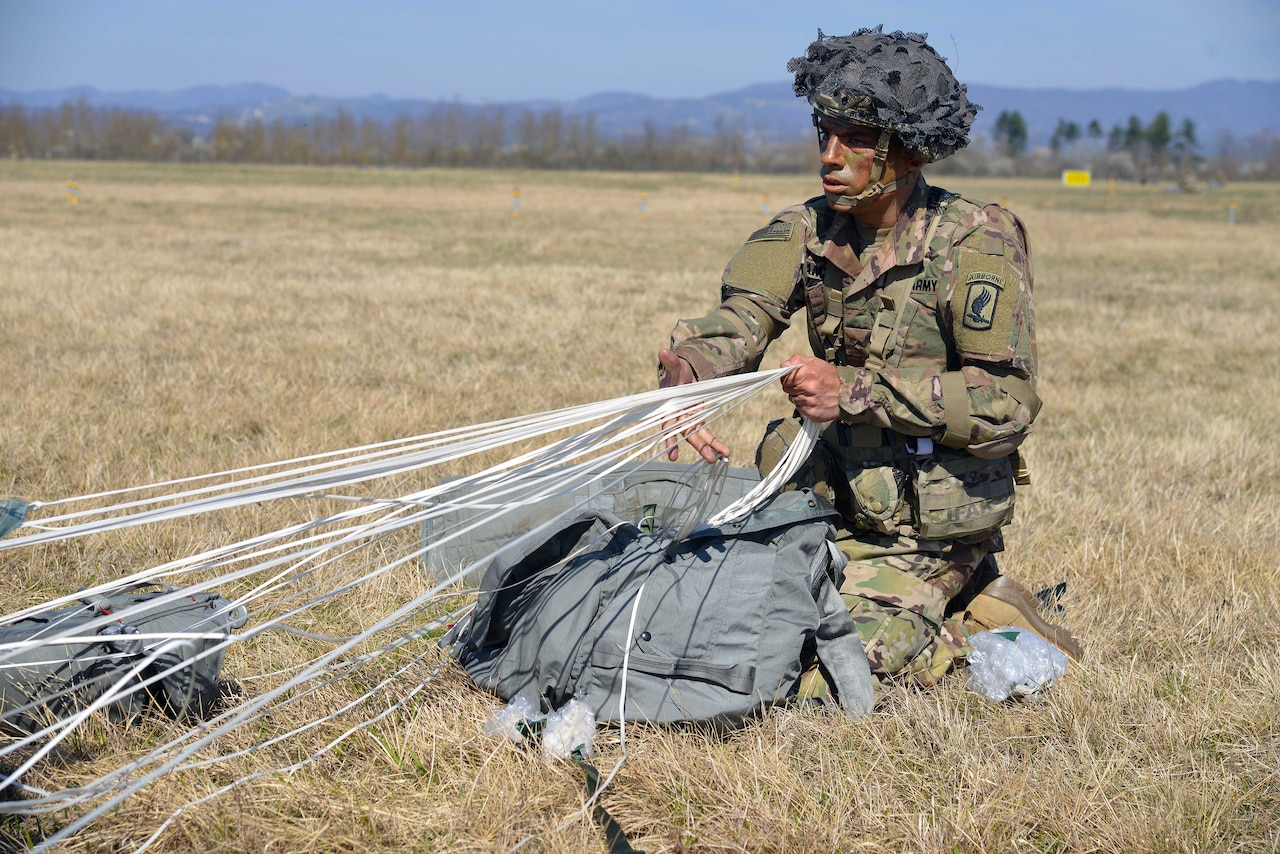 A paratrooper secures his equipment after a jump.