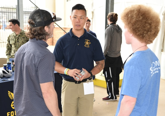Petty Officer 1st Class Yong Yo (center), a special warfare scout assigned to Navy Recruiting District San Antonio, speaks with attendees about career opportunities in America's Navy during the 92nd Clyde Littlefield Texas Relays held at the Mike A. Myers Stadium on the campus of the University of Texas in Austin.
