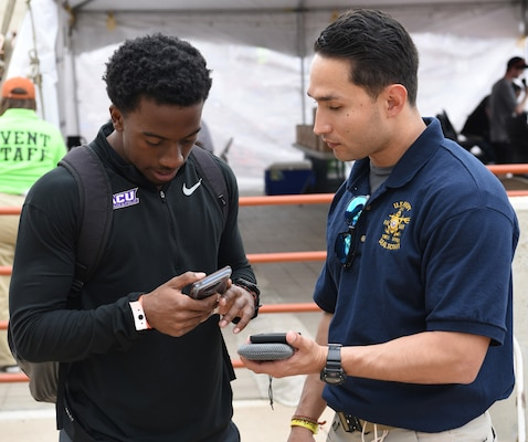 Petty Officer 2nd Class Dectorio Huerta (right), a special warfare scout assigned to Navy Recruiting District San Antonio, assists an athlete with submitting contact information during the 92nd Clyde Littlefield Texas Relays held at the Mike A. Myers Stadium on the campus of the University of Texas in Austin. The meet, which ran from March 27-30, welcomed more than 7,000 athletes in the high school, collegiate and professional ranks.