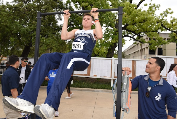 Petty Officer 2nd Class William Sanchez (right), a special warfare scout assigned to Navy Recruiting District Dallas, monitors an athlete in a pull-up challenge during the 92nd Clyde Littlefield Texas Relays held at the Mike A. Myers Stadium on the campus of the University of Texas in Austin. The meet, which ran from March 27-30, welcomed more than 7,000 athletes in the high school, collegiate and professional ranks. The recruiters and Warrior Challenge Mentor Program personnel from Navy Recruiting Districts Dallas, San Antonio, and Houston attended to spread Navy Awareness and to speak with athletes about pursuing a career in America's Navy.