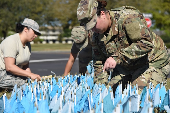U.S. Air Force Staff Sgt. Cheyenne Green, 81st Training Support Squadron curriculum developer, (right) and Staff Sgts. Julie Minjarez, 85th Engineering Installation Squadron project manager, and Lionyann Maynard, 85th EIS radio frequency transmissions systems technician, place teal colored flags in the ground for Sexual Assault Awareness Month near the Keesler Base Exchange satellite pharmacy on Keesler Air Force Base, Mississippi, April 2, 2019. Each flag represents five Department of Defense members who reported being sexually assaulted in fiscal year 2017. The 1,354 flag display will be moved to several locations around the base throughout the month. Keesler's Sexual Assault Prevention and Response office provides sexual assault response coordinators and victim advocates to assist victims and survivors of sexual assault. (U.S. Air Force photo by Kemberly Groue)