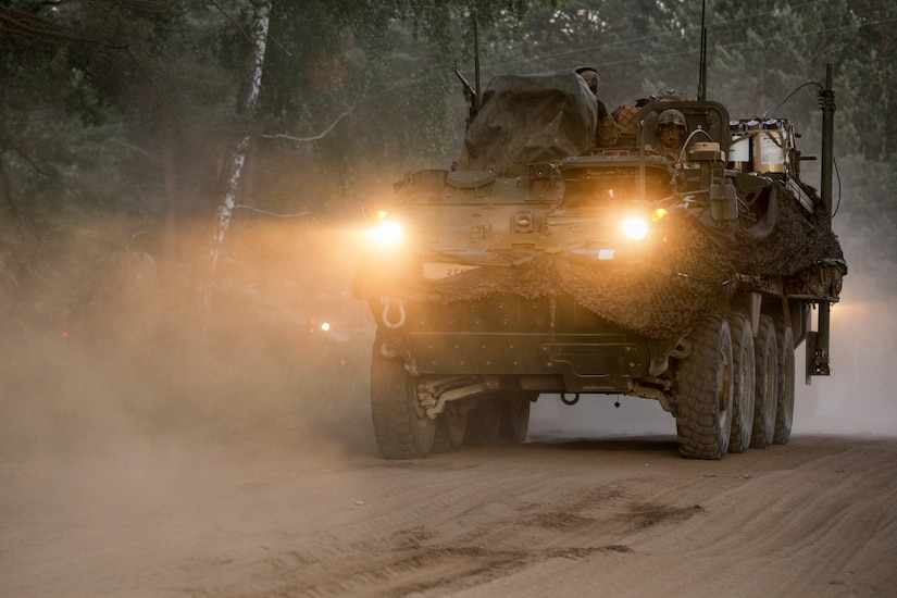 An infantry carrier vehicle moves on a dusty road.