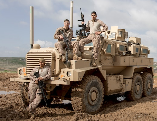 U.S. Marine Corps Sgt. Naomi L. Polumbo, left, Lance Cpl. Jacob Walton, center, motor transport mechanics, and Lance Cpl Edgar Garcia, right, a small arms repairman, all with Combat Logistics Detachment 34, attached to Special Purpose Marine Air-Ground Task Force Crisis Response-Central Command, pose for a photo with a mine resistant, ambush protected vehicle, Southwest Asia, February 10, 2019. As a quick reaction force, the SPMAGTF-CR-CC is capable of deploying aviation, ground and logistical forces forward at a moment's notice.