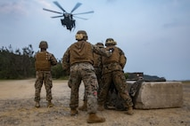U.S. Marines Corps landing support specialists with Headquarters and Service Company, Combat Logistics Battalion 4, Combat Logistics Regiment 3, 3rd Marine Logistics Group, prepare a training block to be lifted by a CH-53E Super Stallion helicopter on Landing Zone Swan, Okinawa, Japan March 29, 2019. Helicopter support team operations are conducted to train landing support specialists and pilots for transferring heavy equipment and supplies using helicopters.