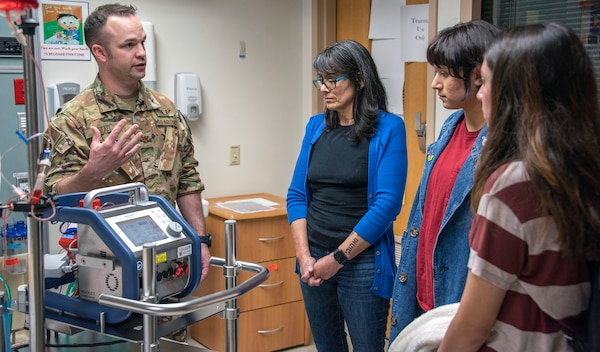 Air Force Maj. (Dr.) Matthew Read, acting Extracorporeal Membrane Oxygenation medical director, demonstrates the ECMO machine for Rita Ibanez and her children at Brooke Army Medical Center, Fort Sam Houston, Texas, March 22, 2019. The adult ECMO mission began at BAMC in 2012. Today, a designated team of Army, Air Force and Navy physicians, nurses, technicians and program managers is able to provide round-the-clock care to four patients simultaneously.