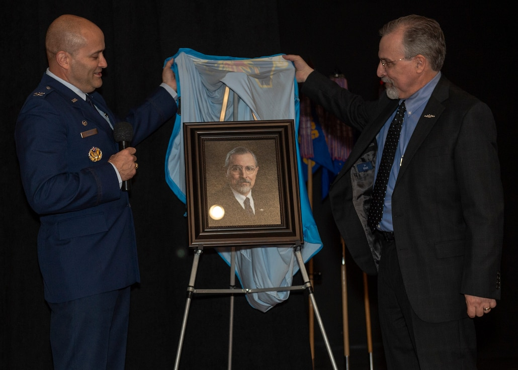 U.S. Air Force Col. Eric Carney, 97th Air Mobility Wing commander, and Jim Gover, president of Lending and Corporate Security Officer at NBC Bank in Altus, unveil Gover's portrait during the friends of Altus Induction Ceremony, March 29, 2019, at Altus Air Force Base, Okla. Gover previously served in the U.S. Navy and remains an avid supporter of the armed services. (U.S. Air Force Photo by Senior Airman Jackson N. Haddon)